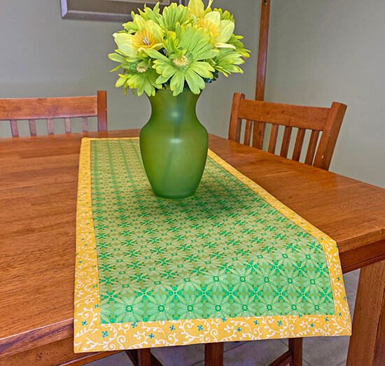 Learn How to Make a No-Hassle Table Topper Table Runner with Mitered Corners with our No-Hassle Table Topper Sewing Tutorial at The Nancy Zieman Productions Blog