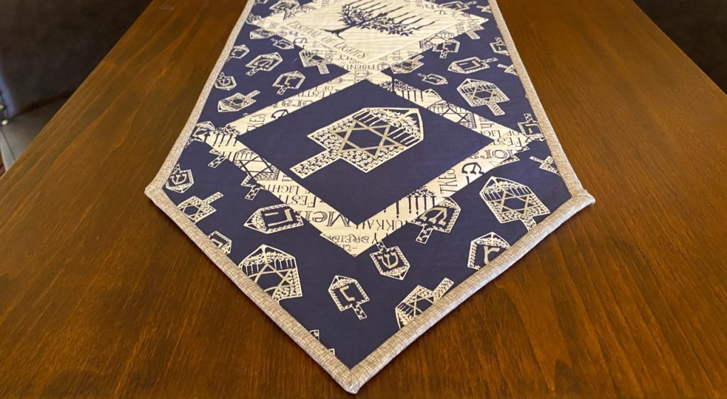 Stitch a Festival of Lights Table Runner with a Convenient Pre-Printed Fabric Panel